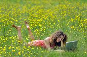Cute young woman with curly hair lying reading a book in a wildflower meadow full of colorful yellow