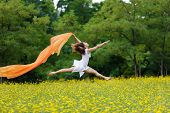 Agile barefoot woman with curly brown hair leaping in the air in a meadow of yellow wildflowers trai