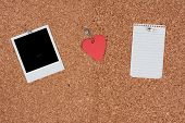 A message cork board with a blank photo, a paper heart and blank sheet of paper held up with push pi