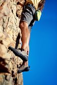 Cropped image of a man's legs finding a foothold while rock climbing