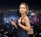 party, celebration, holiday and banking concept - beautiful woman in evening dress with small bag an
