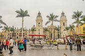 LIMA, PERU, MAY 23, 2014 - Horse drawn carriage waits for tourists in Plaza Mayor with Cathedral de Lima in background