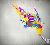 Close up of hand splashing colorful paint from colorful bucket