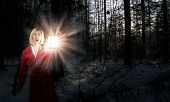 Young woman in red cloak with lantern lost in forest
