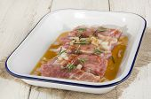 stock photo of marinade  - ribs with rosemary and marinade in a bowl - JPG
