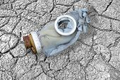 image of chemical weapon  - Dirty broken gas mask on cracks symbolizing the  - JPG