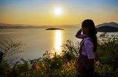 stock photo of chan  - Happy young woman standing on the hill watching the sunset over the lake in Kaeng Kra Chan National Park Phetchaburi Province Thailand