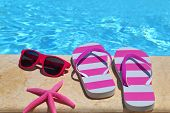 Flip flops, glasses and starfish by the poolside