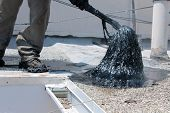 picture of tar  - Unidentifiable workers use  - JPG