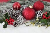 Christmas still life with red baubles, snow, holly, pine cones, mistletoe and fir .