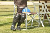 TSELEEVO, MOSCOW REGION, RUSSIA - JULY 26, 2014: Equestrian helmet and riding boots with kneepads on the folding chair during the British Polo Day. It was the second British Polo Day in Russia