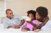 foto of babygro  - Happy parents with baby girl on their bed at home in the bedroom - JPG