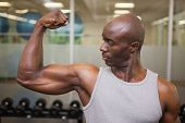 Portrait of a muscular man flexing muscles in gym