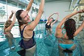 stock photo of day care center  - Female fitness class doing aqua aerobics on exercise bikes in swimming pool at the leisure centre - JPG