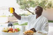 Handsome man in bathrobe having breakfast outside on a sunny day