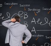 Thinking businessman against blackboard with business buzzwords