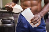 stock photo of muscle builder  - Mid section of a body builder holding a scoop of protein mix in gym - JPG
