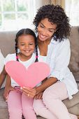 Pretty mother sitting on couch with daughter reading heart card at home in the living room
