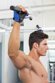 Side view of a shirtless male body builder doing pull ups at the gym