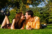 The Happy Young Couple Kisses On A Grass