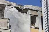 ASHKELON, ISRAEL - JANUARY 10, 2009: Hole in the roof,  broken windows and damaged apartment after direct hit and explosion of the rocket  launched by Hamas terrorists from Gaza strip.