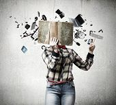 Woman in casual wear hiding her face behind book