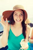 summer holidays, vacation and celebration concept - smiling girl in hat with champagne glass