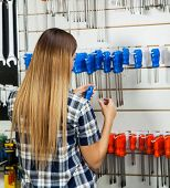 Rear view of female customer selecting screwdriver in hardware shop