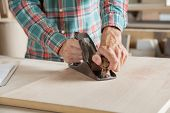 Midsection of male carpenter using planer on wood in workshop