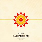 Beautiful rakhi on beige background for Happy Raksha Bandhan festival celebrations.