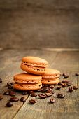 Row of coffee macarons on a table with coffee beans