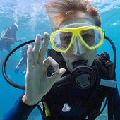 Female scuba diver underwater showing ok signal