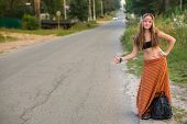 Young hippie girl with backpack hitchhiking on countryside road.