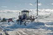stock photo of power-shovel  - Grader removes snow from road after storm - JPG