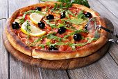 Tasty pizza with herbs and round knife on board and wooden table background