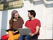Two College Students Talking And Working Outdoors On Laptop