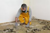 foto of putty  - Adult worker with protective mask remove glue and rubber with putty knife from floor - JPG