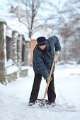 picture of shovel  - Caucasian woman cleaning snow from sidewalk with shovel - JPG