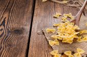 Raw Farfalle (on Wooden Background)