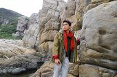 young man in scarf with coat sitting on a rock at beach