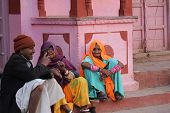 Three Indians sit outside a pink building in Jaipur