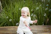 Adorable Little Girl Sitting On Bench Having Fun With Bubbles Outside.