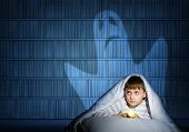 foto of boys night out  - image of a boy under the covers with a flashlight the night afraid of ghosts - JPG