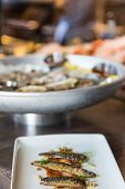 pic of oyster shell  - A plate of sardines with oysters on the half shell in background - JPG