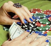 hands of young caucasian woman with blue manicure at casino table close up