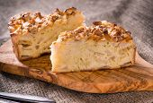 foto of cinnamon  - Homemade apple pie with cinnamon and nuts on olive wood board rustic style selective focus - JPG