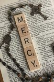 stock photo of bible story  - The word mercy displayed on a Bible with a rosary next to a story about Jesus mercy - JPG