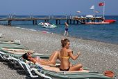Antalya Resort Beach With Sun Loungers, Berth, And Sunbathers People.