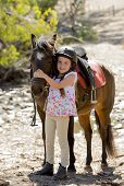 image of horse girl  - sweet beautiful young girl 7 or 8 years old hugging head of little pony horse smiling happy wearing safety jockey helmet posing outdoors on countryside in summer holiday - JPG