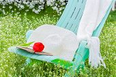 foto of panama hat  - Deckchair tulip scarf and hat in the spring garden against the backdrop of cherry blossoms